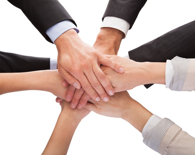 Close-up Of Businesspeople Hands Stacking Together Over White Background